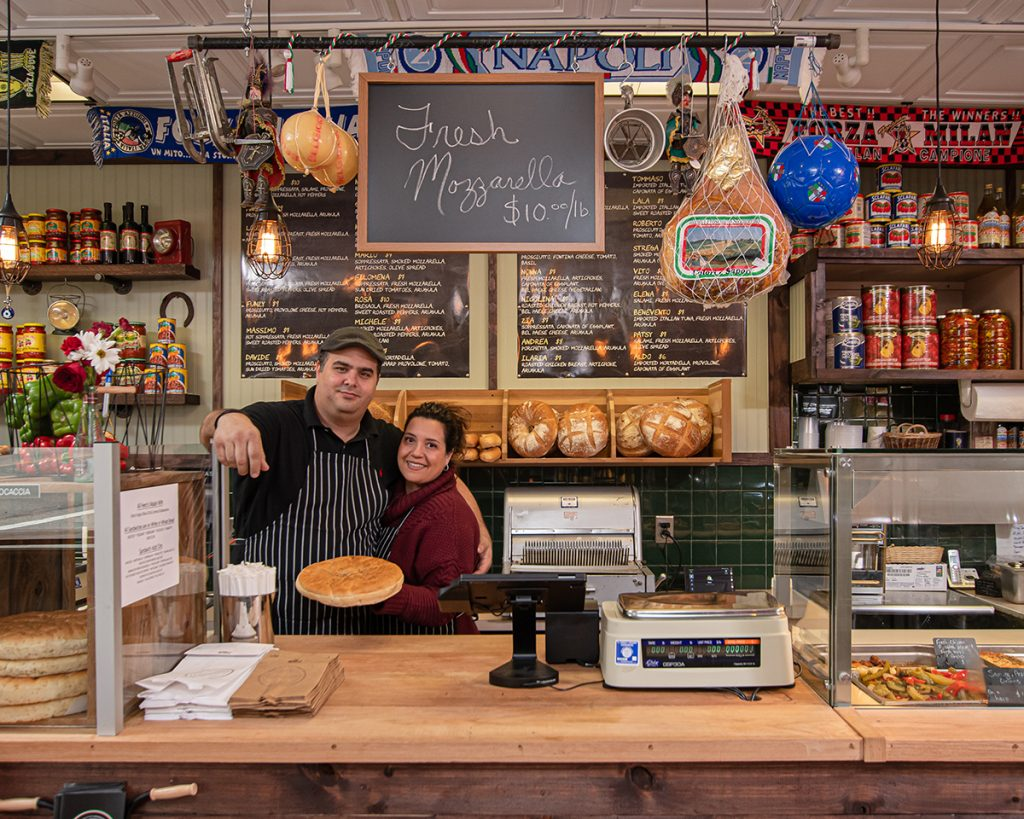 The owners annamaria and tim side by side behind the counter with Annamaria holding a pie